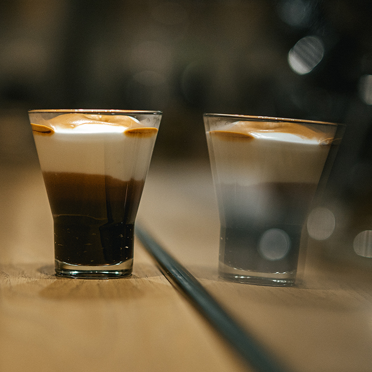 A small glass of a drink with layers of espresso, drinking chocolate and crema, and a reflection of the drink